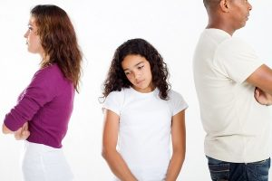 unhappy girl standing between divorcing father and mother in St Louis