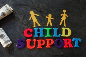 Some rolls of money, the words CHILD SUPPORT spelled out in colorful magnetic letters and three person shapes to pose the questions, how much does a child support lawyer cost in St. Louis Missouri?